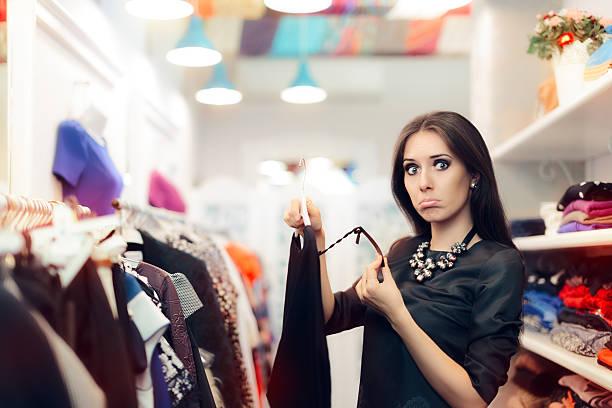 woman checking price tag on sale in clothing store - kleider günstig kaufen stock-fotos und bilder