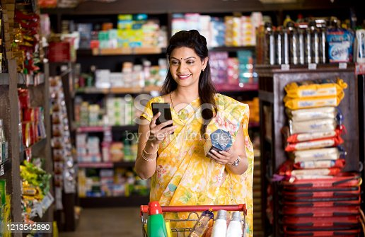 Woman checking product details online using mobile phone at grocery store