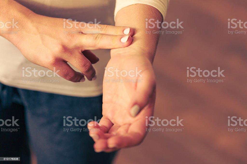 Woman checking pulse on wrist closeup stock photo