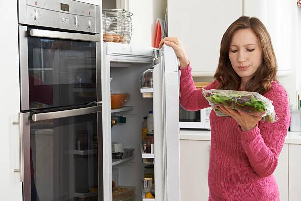 Mujer comprobación de venta por fecha de una ensalada bolsa en el refrigerador - foto de stock