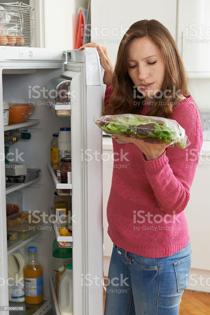 Woman Checking Sell By Date On Salad Bag In Refrigerator stock photo