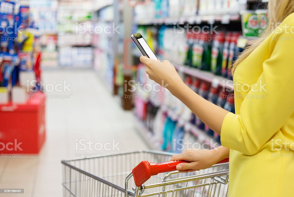 Woman checking shopping list on her smartphone stock photo