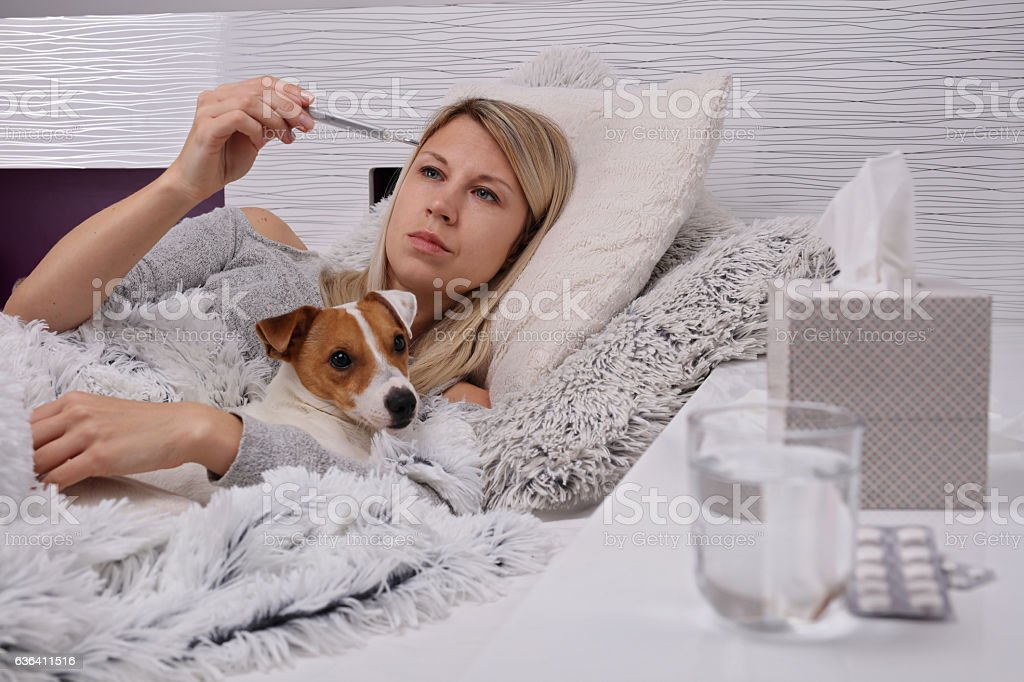 Woman checking temperature with thermometer. Flu, cold, headache, running nose. stock photo