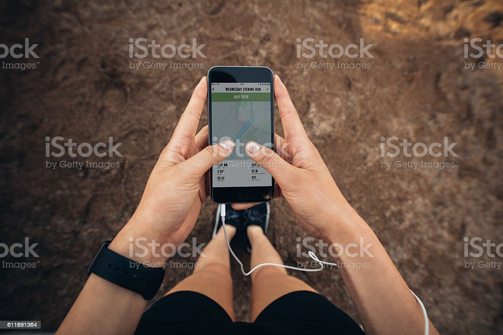 Woman checking the summary of her run on smartphone stock photo