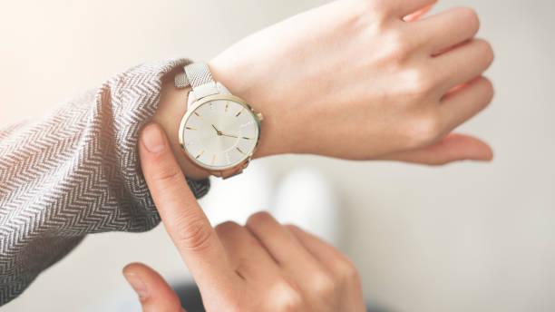 vrouw controleren tijd haar horloge - wijzerplaat stockfoto's en -beelden