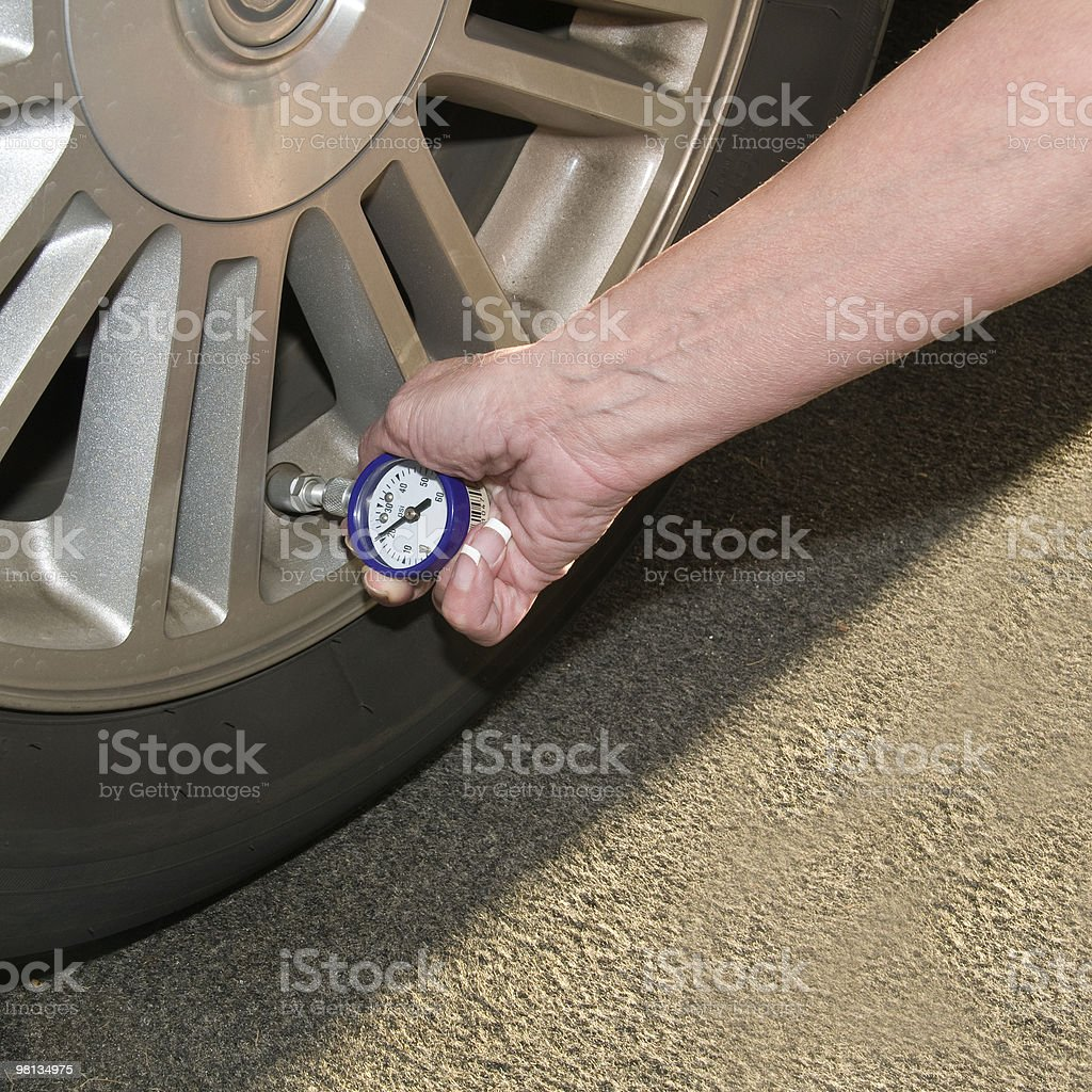 Woman checking tire pressure royalty-free stock photo