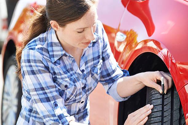 Mujer de verificación en automóvil de rodadura de los neumáticos con manómetro - foto de stock
