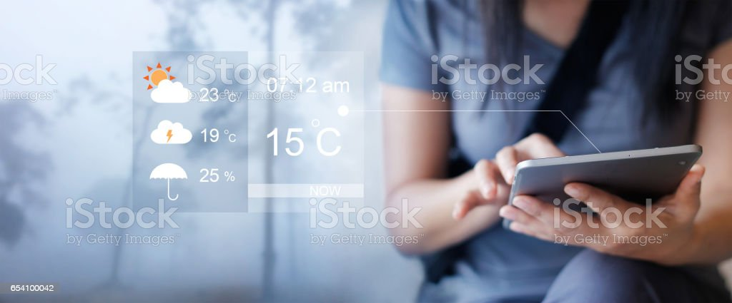 Woman checking up the weather forecast from tablet application stock photo