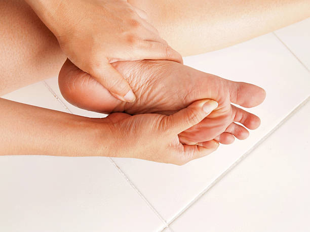 woman checks her aching foot - human foot stock photos and pictures