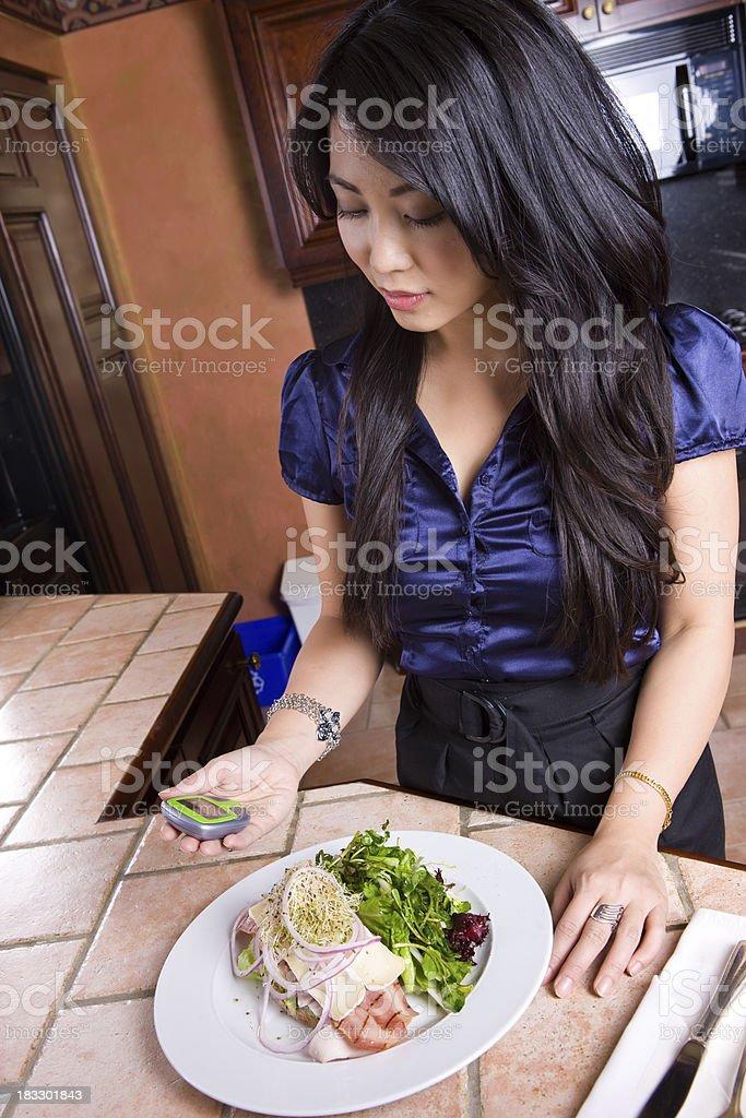 Woman Checks Her Blood Sugar In Modern Kitchen royalty-free stock photo