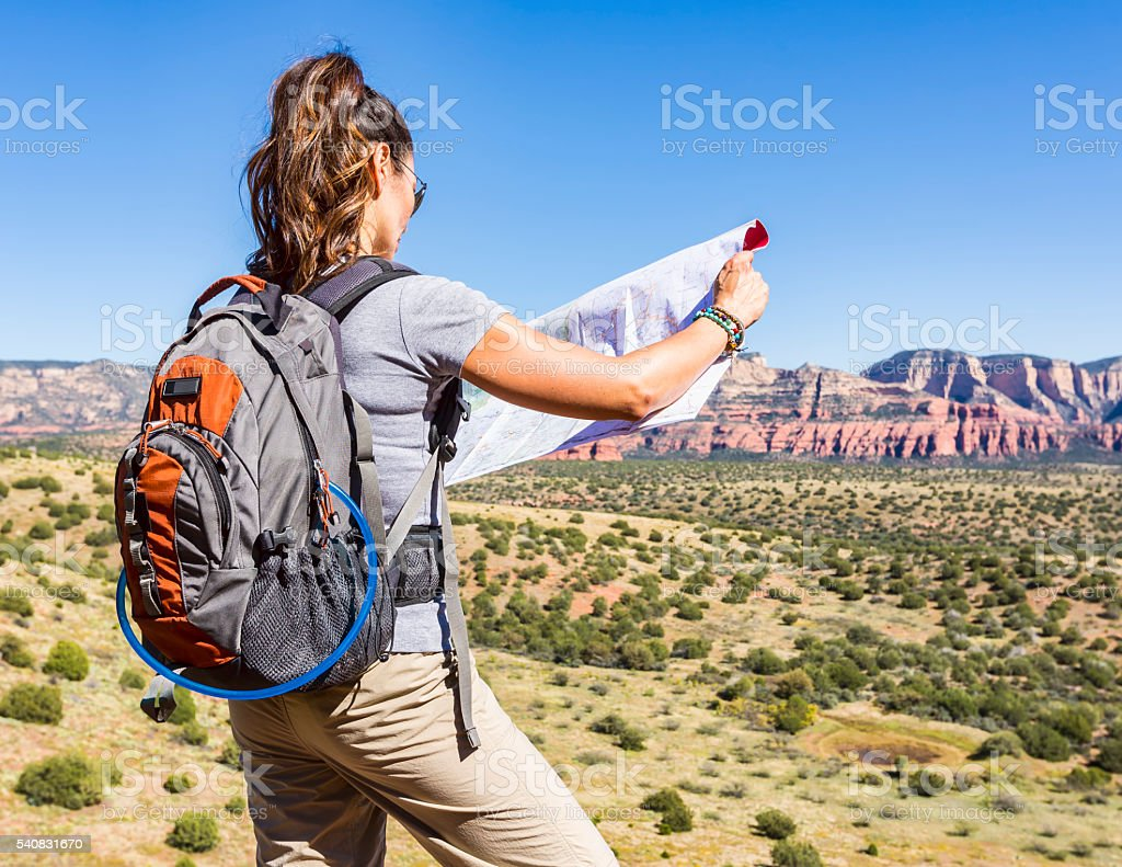 Woman Checks Map While Hiking Outdoors stock photo