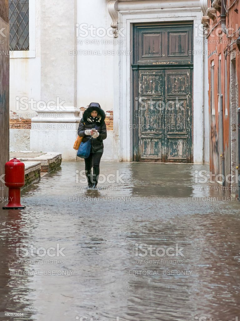 Woman checks mobile phone whilst walking through the acqua alta stock photo