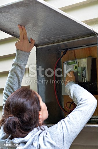 istock Woman checks the electric meter. 693910734