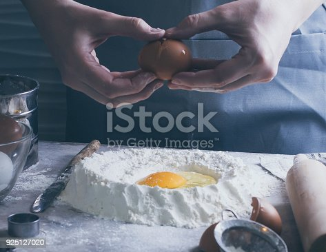 istock Woman Chef broken egg in flour. Ingredients for dough making. Bakery or Baking Concept. 925127020