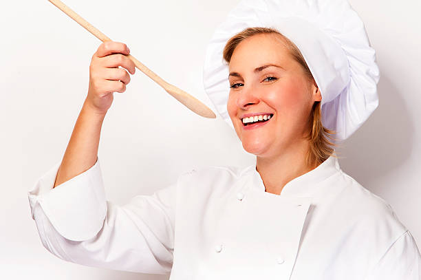Woman chef holding a spoon and tasting from spoon. stock photo