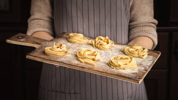Woman chef holding wooden board with fettuccine nests Woman chef holding wooden cutting board with yellow fettuccine nests on kitchen uncooked pasta stock pictures, royalty-free photos & images