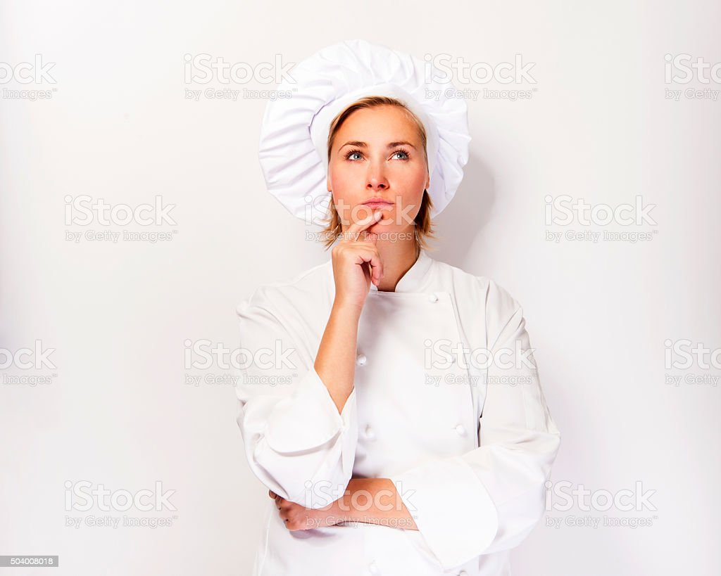 Woman chef look up and thinking. stock photo