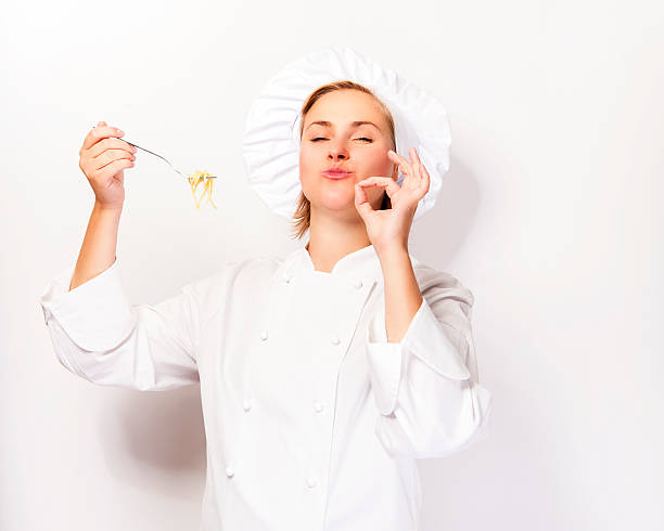 Woman chef showing a sign perfect, with pasta noodle. stock photo