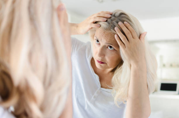 Woman cheking hair in front of mirror stock photo