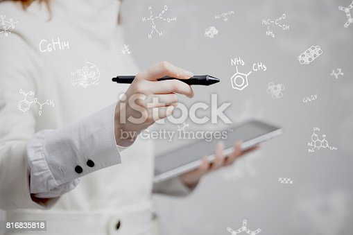 istock Woman chemist working with chemical formulas on grey background 816835818