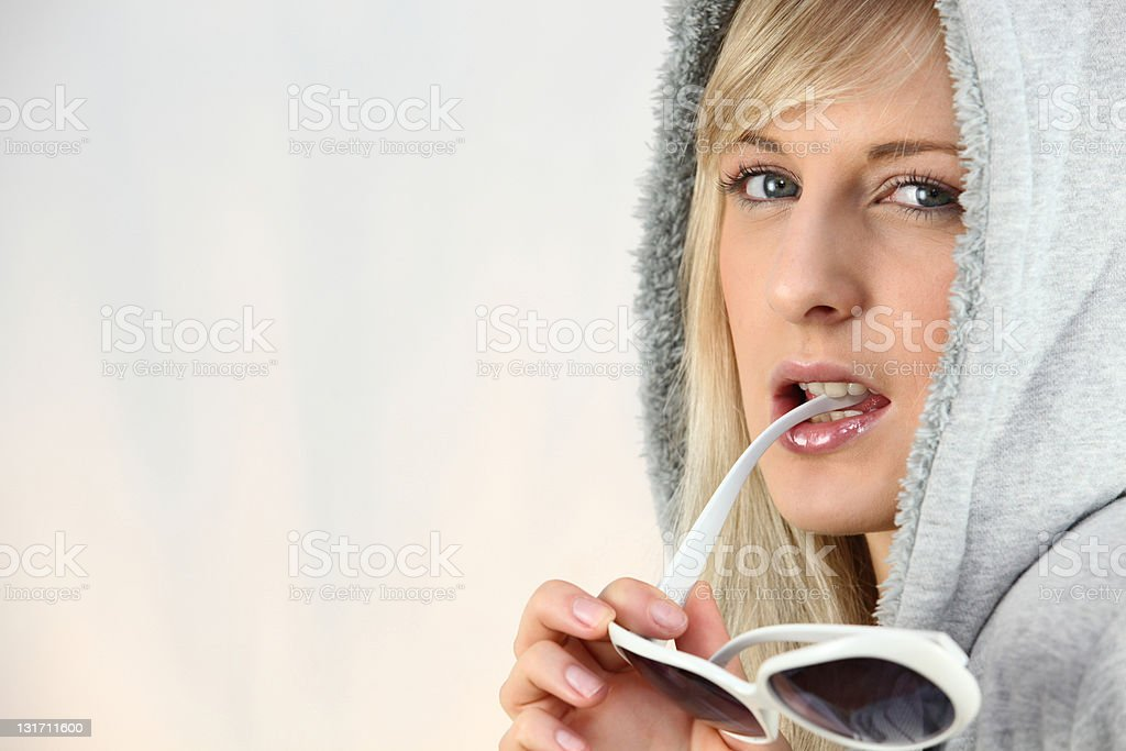 Woman chewing on her sunglasses stock photo