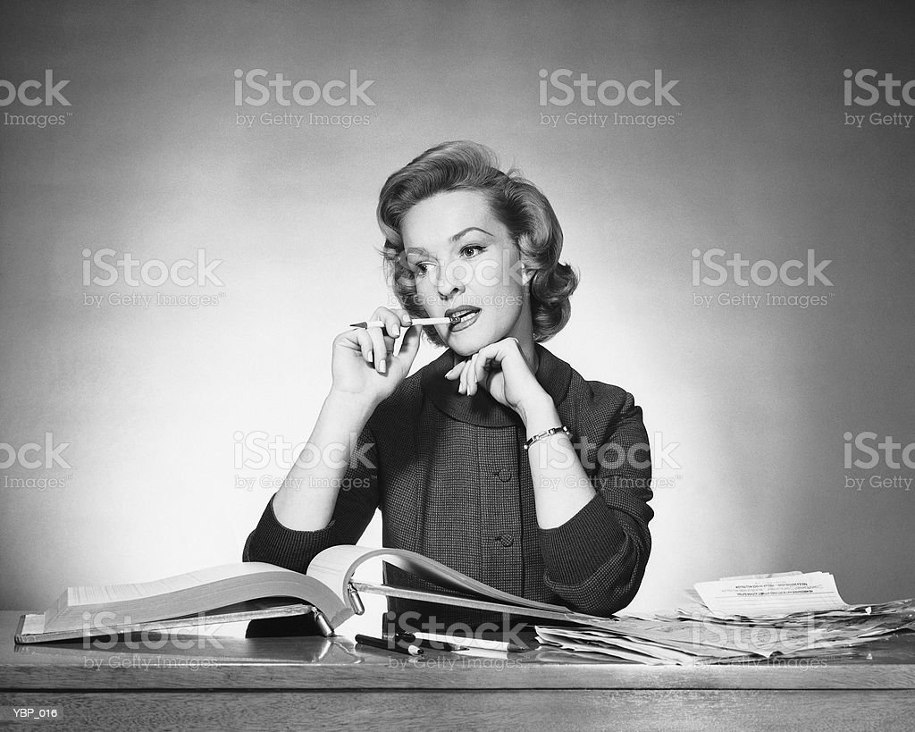Woman chewing on pencil, book open in front of her royalty free stockfoto