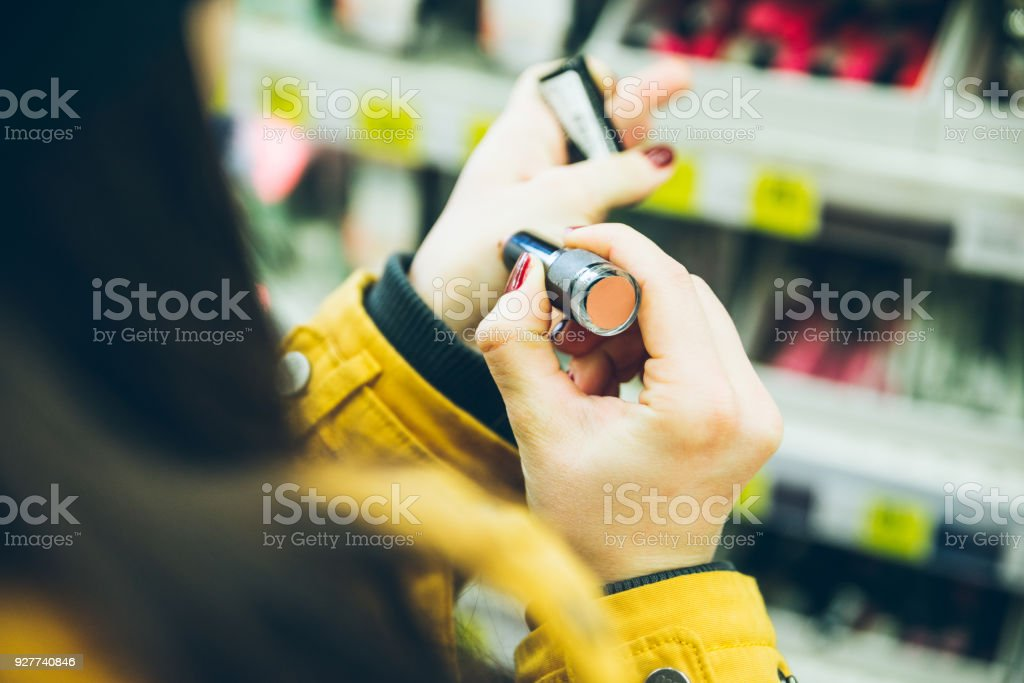 woman choose lipstick in store close up