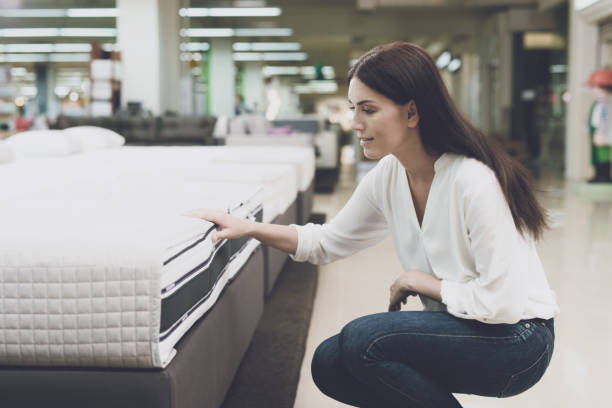 a woman chooses a mattress in a store. she sits next to him and examines him - furniture shopping stock photos and pictures