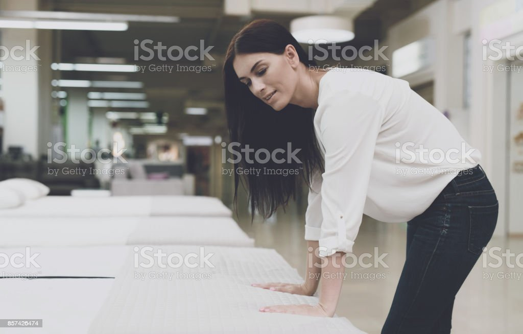A woman in a white shirt and jeans in a mattress store. She examines...