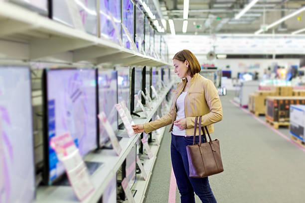 frau wählt einen fernseher im store - freizeitelektronik stock-fotos und bilder