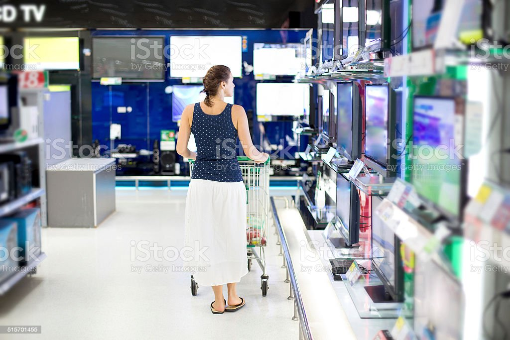 woman chooses a TV in the store stock photo