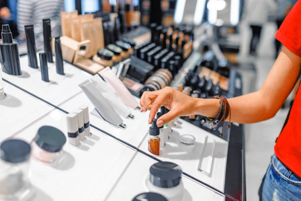 woman chooses cosmetics and make-up products in a store - make up imagens e fotografias de stock