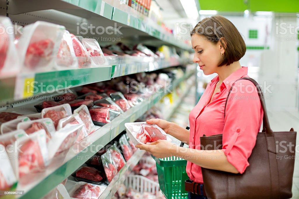 Frau wählt Fleisch im Laden Lizenzfreies stock-foto