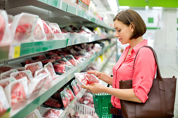 Woman chooses meat in the store stock photo