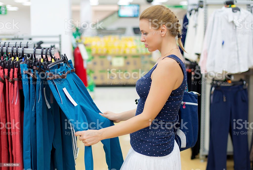 woman chooses pants in the store stock photo