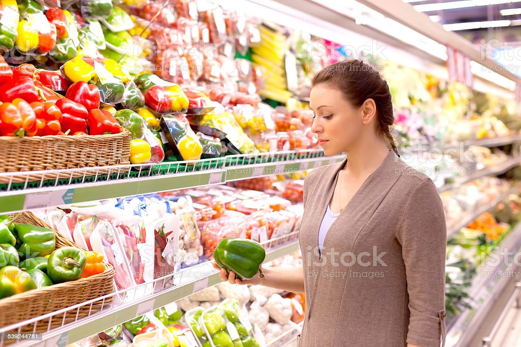 Woman chooses produce in supermarket stock photo