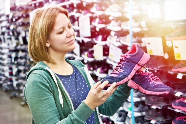 Woman chooses running shoes in store stock photo