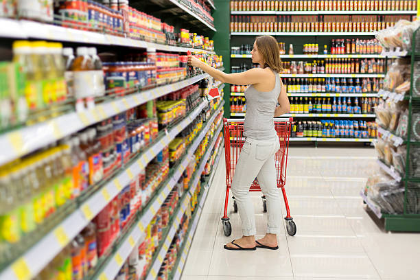 woman chooses sauce in the supermarket woman chooses sauce in the supermarket snack aisle stock pictures, royalty-free photos & images