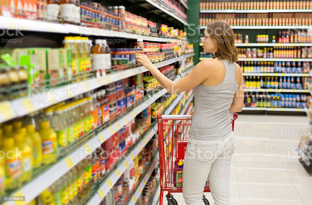 woman chooses sauce in the supermarket stock photo