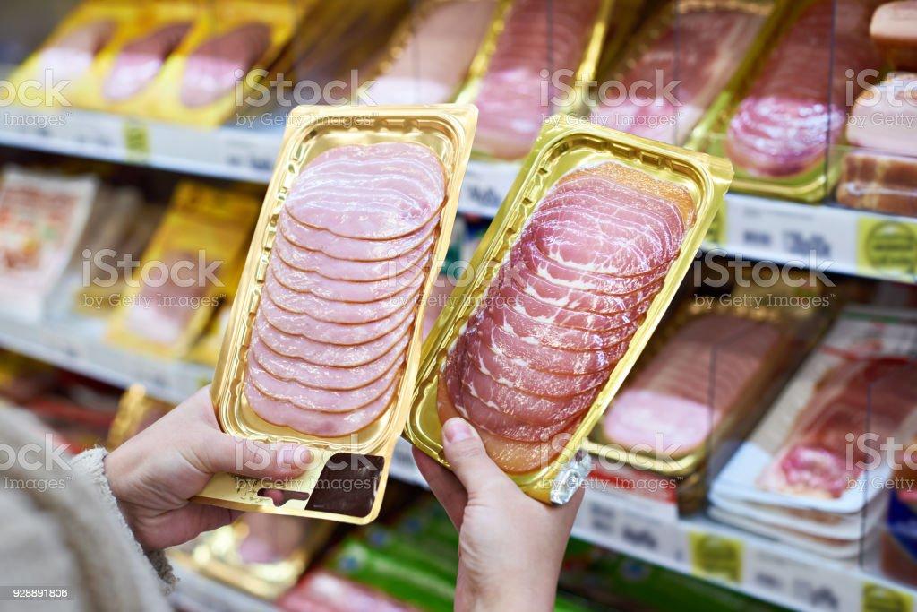 Woman chooses slice of ham at store stock photo