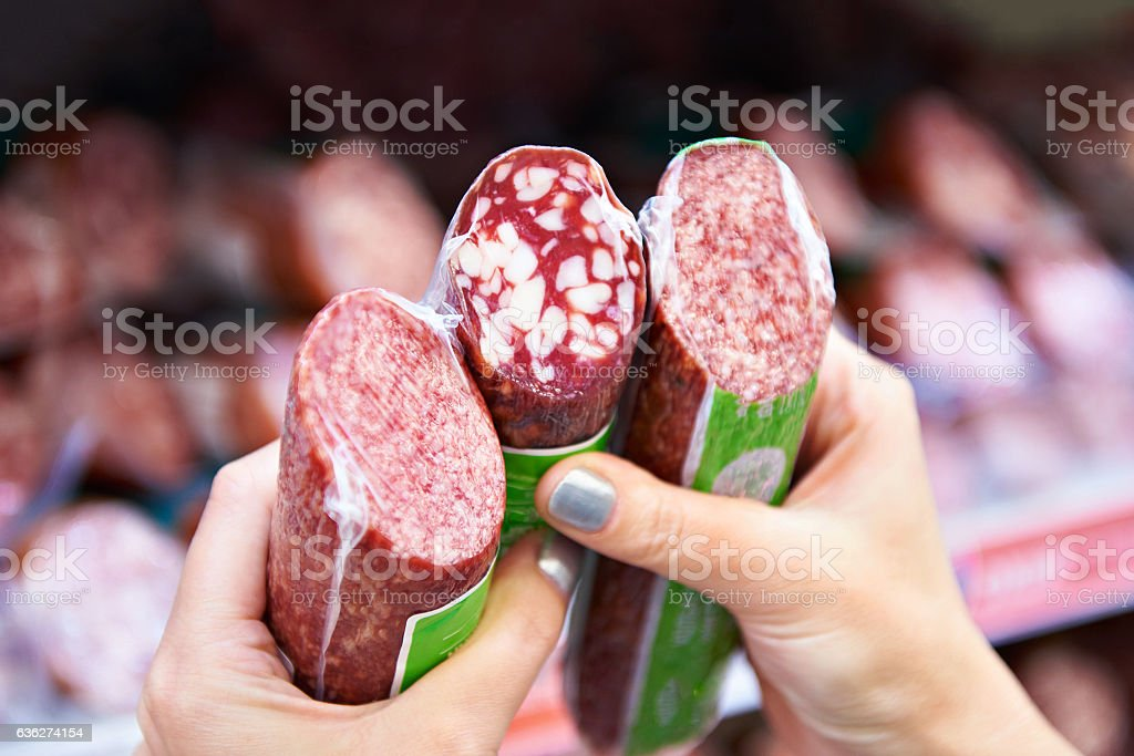 Woman chooses smoked sausage in store stock photo