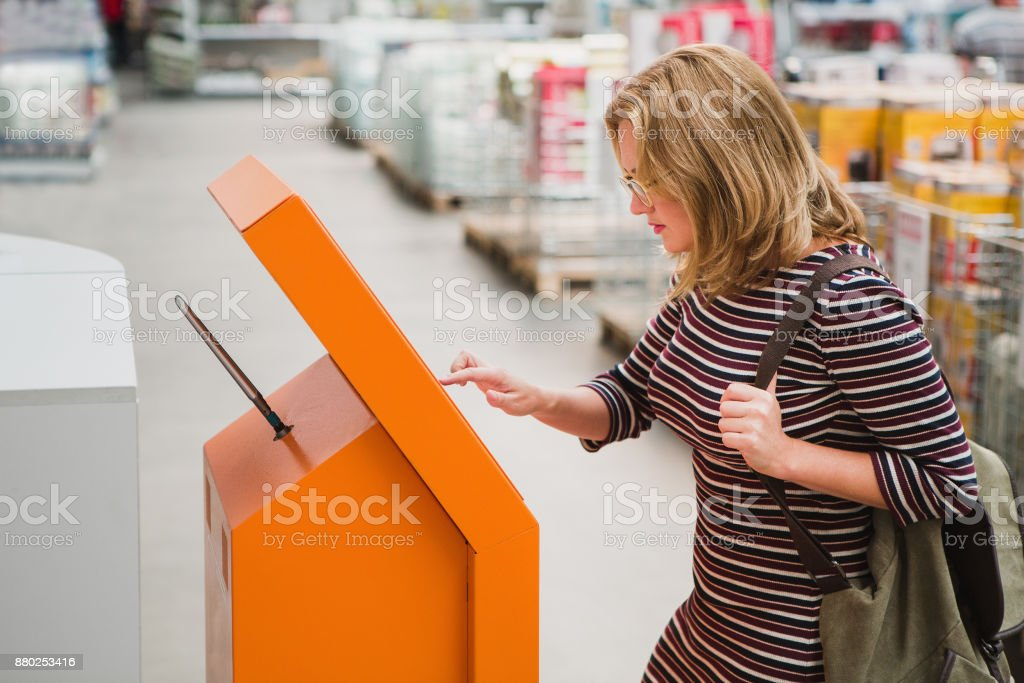 A woman chooses the goods online at the self-service device stock photo