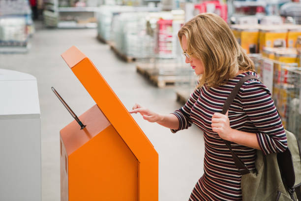 a woman chooses the goods online at the self-service device - interactivity stock photos and pictures