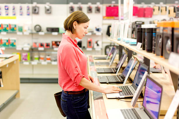 woman chooses the laptop - electronics industry stock pictures, royalty-free photos & images