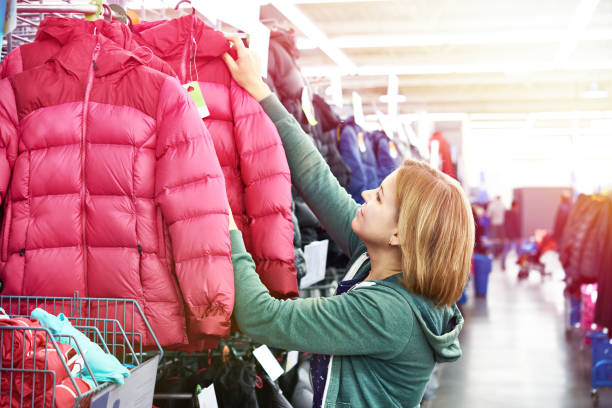 woman chooses winter jacket in store - negozio sci foto e immagini stock