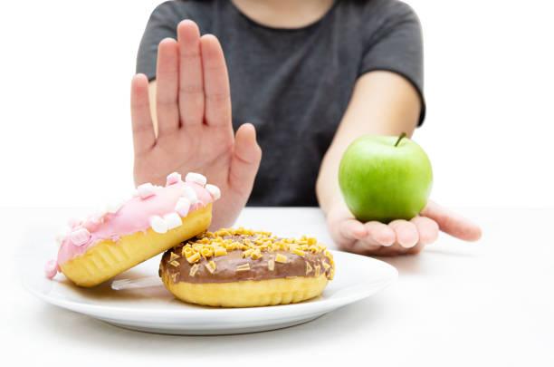 女人在一盤甜甜圈上選擇一個新鮮的蘋果,用手勢拒絕垃圾不健康的食物。特寫,選擇性聚焦。 - 不健康飲食 個照片及圖片檔