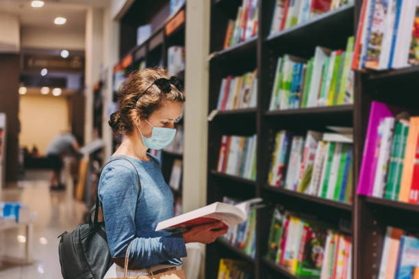 Woman choosing a new book in the bookstore during COVID-19 pandemic stock photo