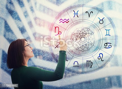 istock Woman choosing a zodiac sign from the astrological wheel to find the future predictions. Having trust in horoscope, consulting stars and believe in the power of universe. Astrology esoteric concept. 1173531652