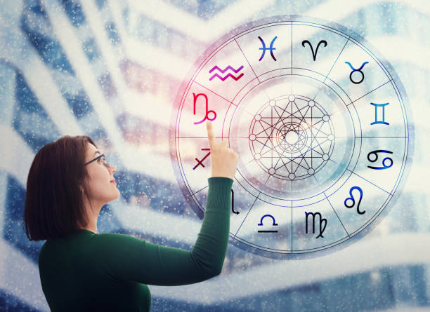 woman choosing a zodiac sign from the astrological wheel to find the future predictions. having trust in horoscope, consulting stars and believe in the power of universe. astrology esoteric concept. - astrologia imagens e fotografias de stock