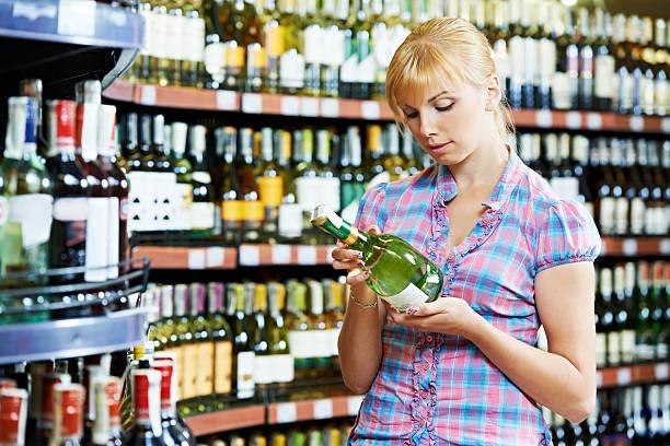 femme choisir et boutiques de vin au supermarché - spiritueux photos et images de collection